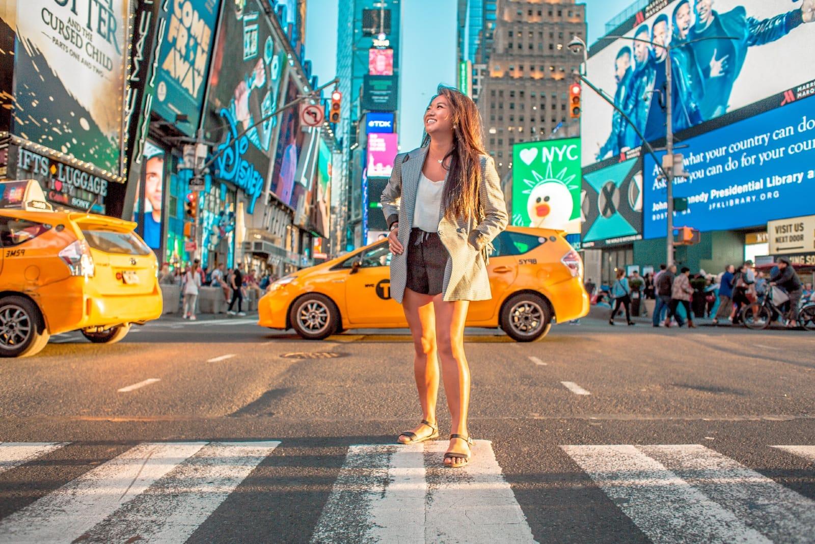 happy woman in gray coat standing on pedestrian lane