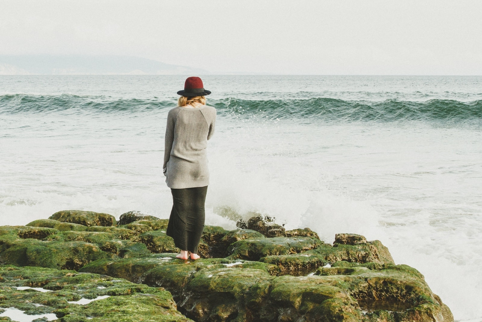 woman with hat standing on rock looking at sea