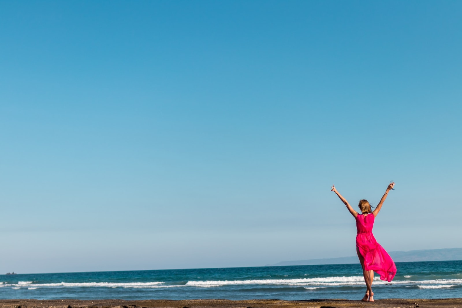 woman in pink dress standing on shore