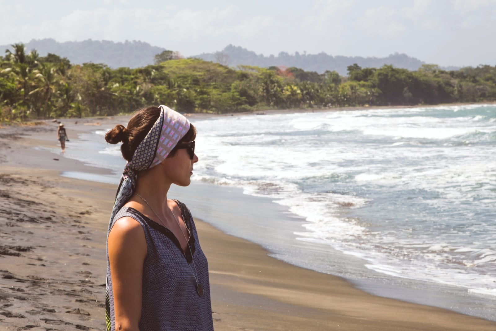woman with head scarf standing on the beach