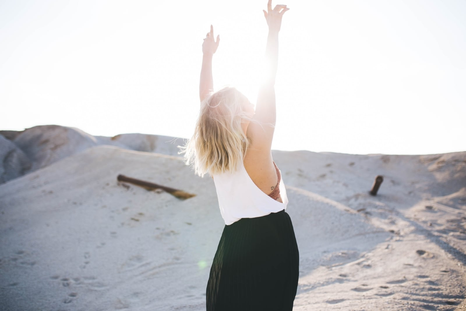 happy woman in white top standing on the desert