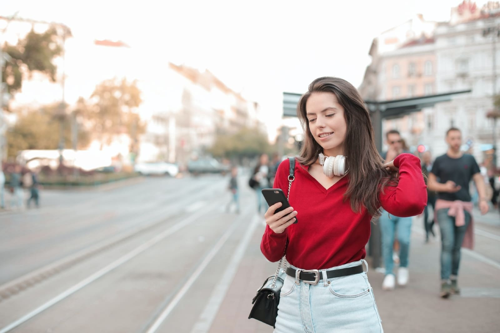 woman looking at phone while standing on street