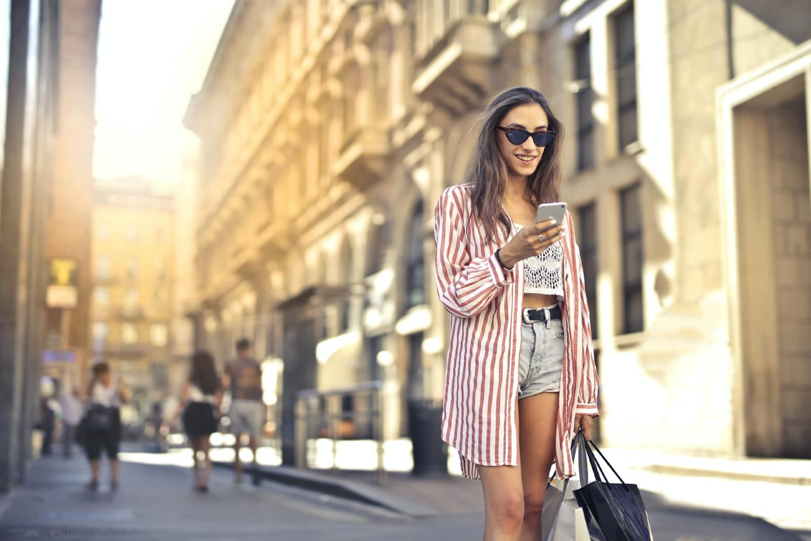 woman using smartphone while standing on the street