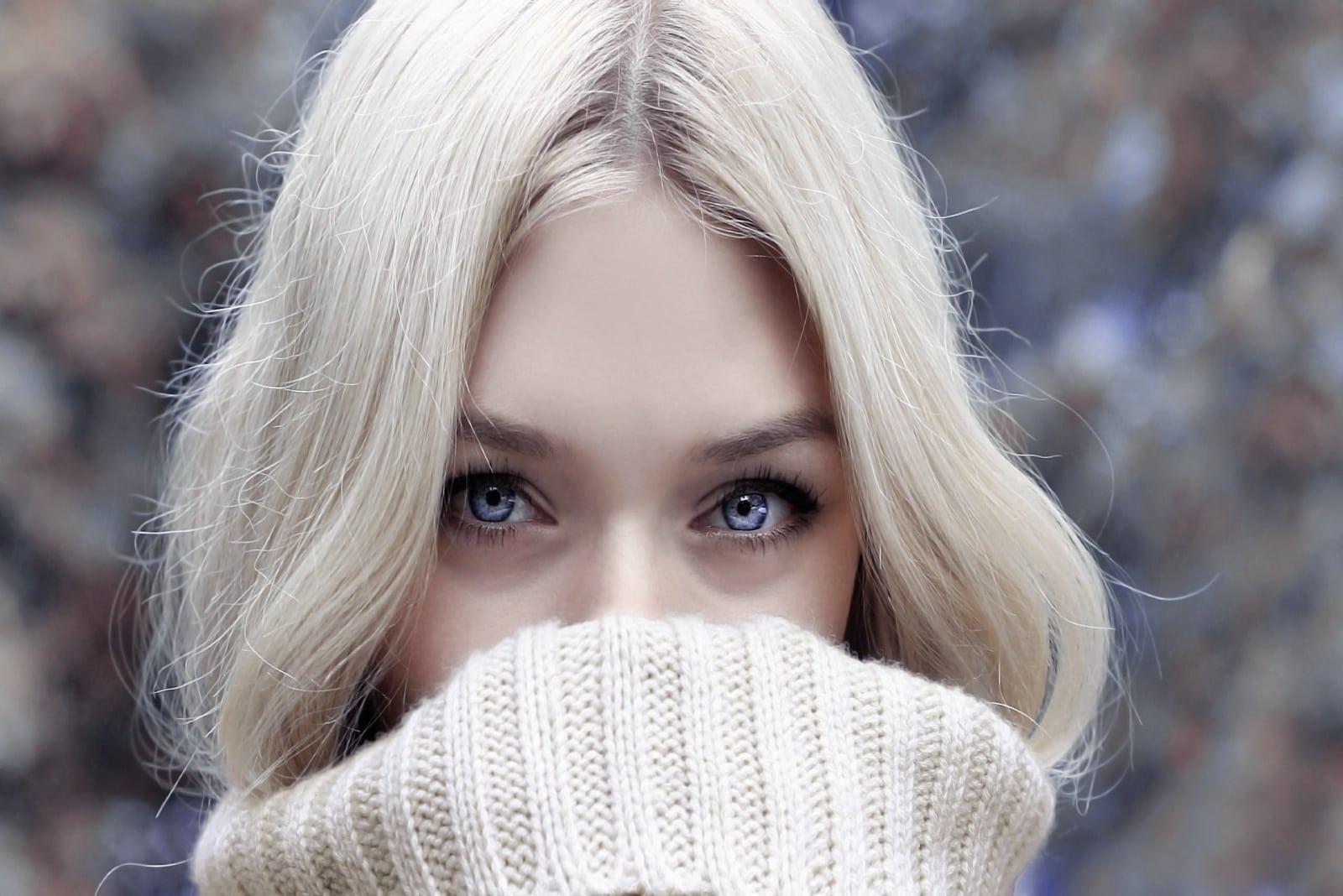 blonde woman in beige turtleneck sweater standing outdoor