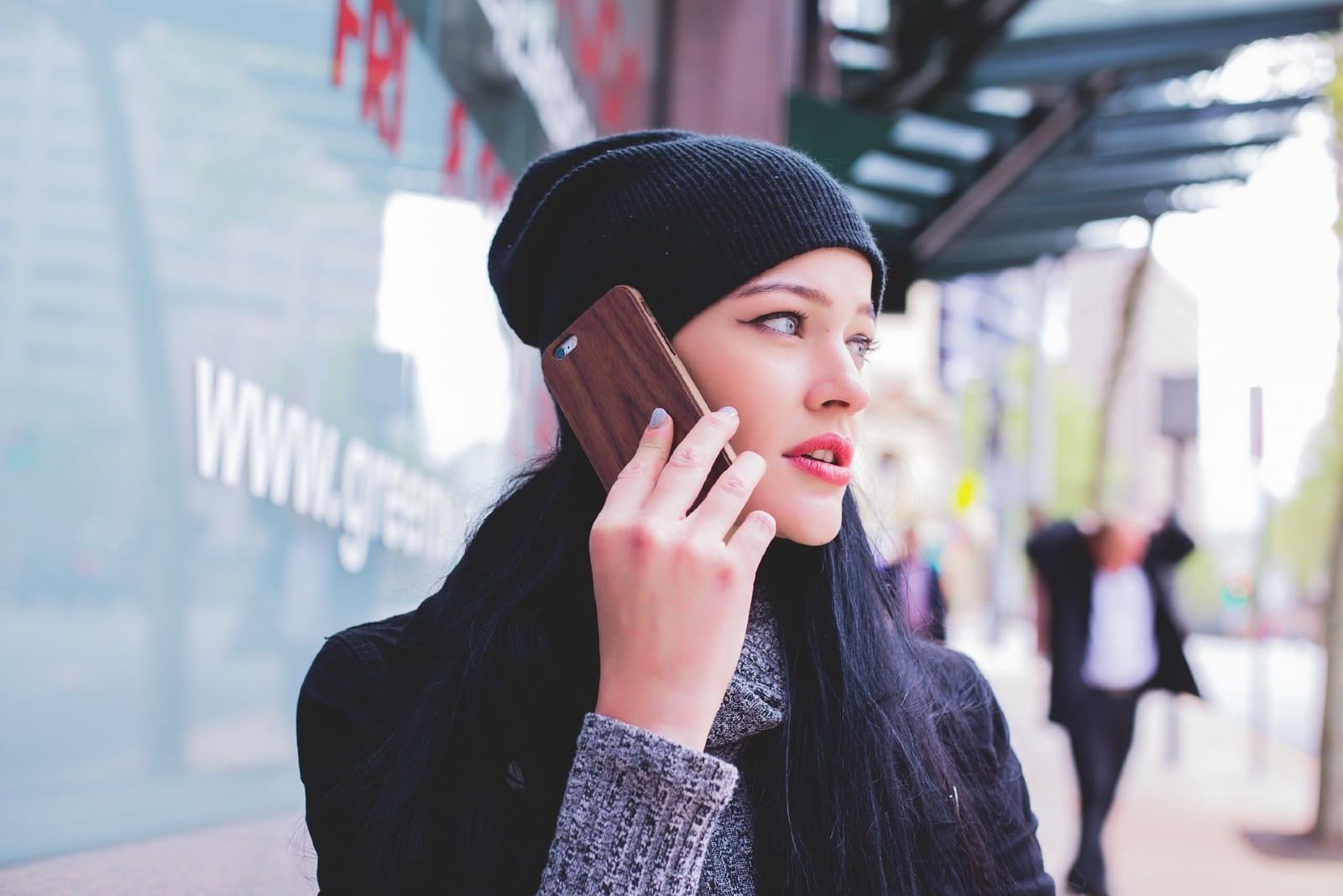 woman with black knit cap talking on the phone outdoor