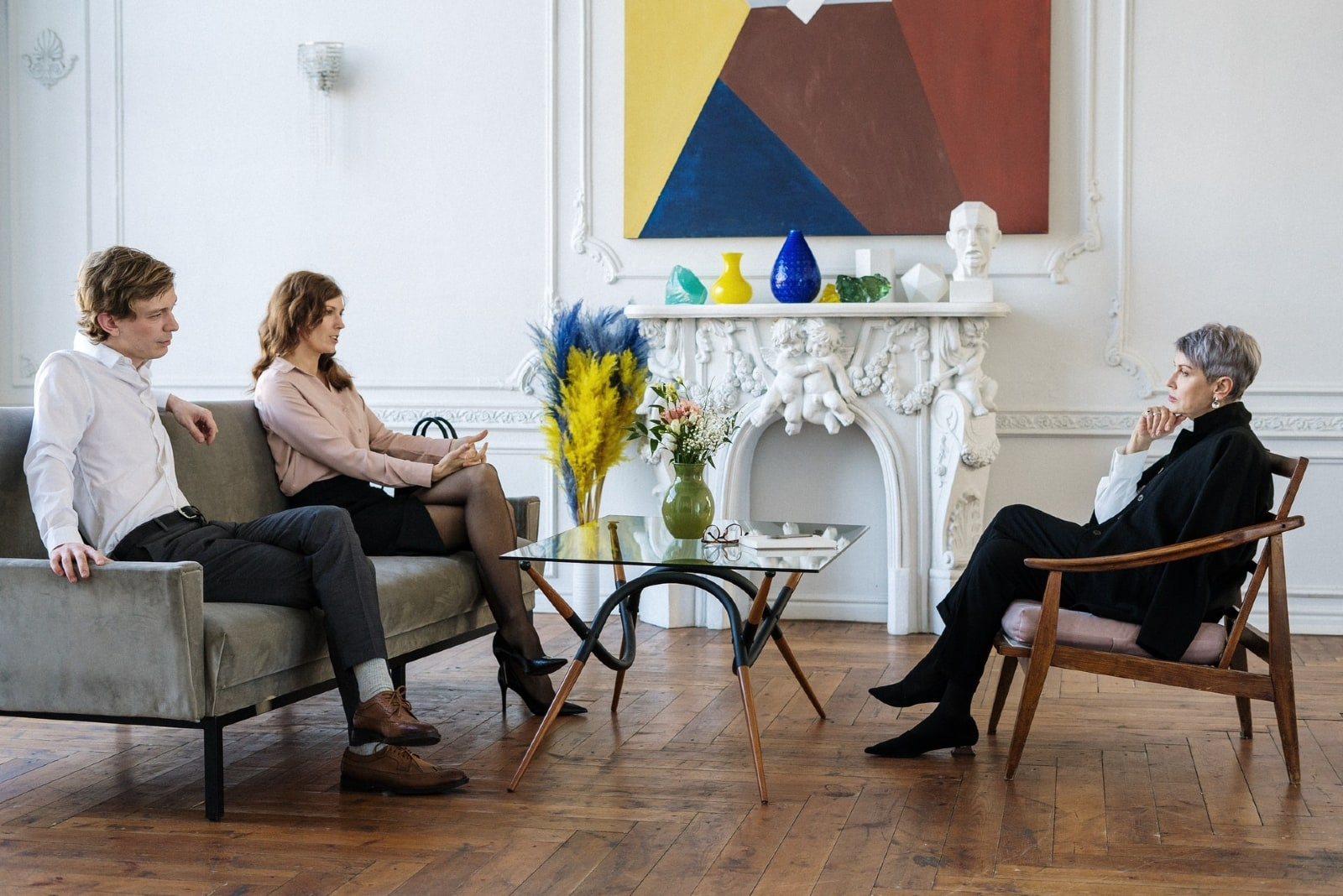 woman talking to therapist while sitting near man