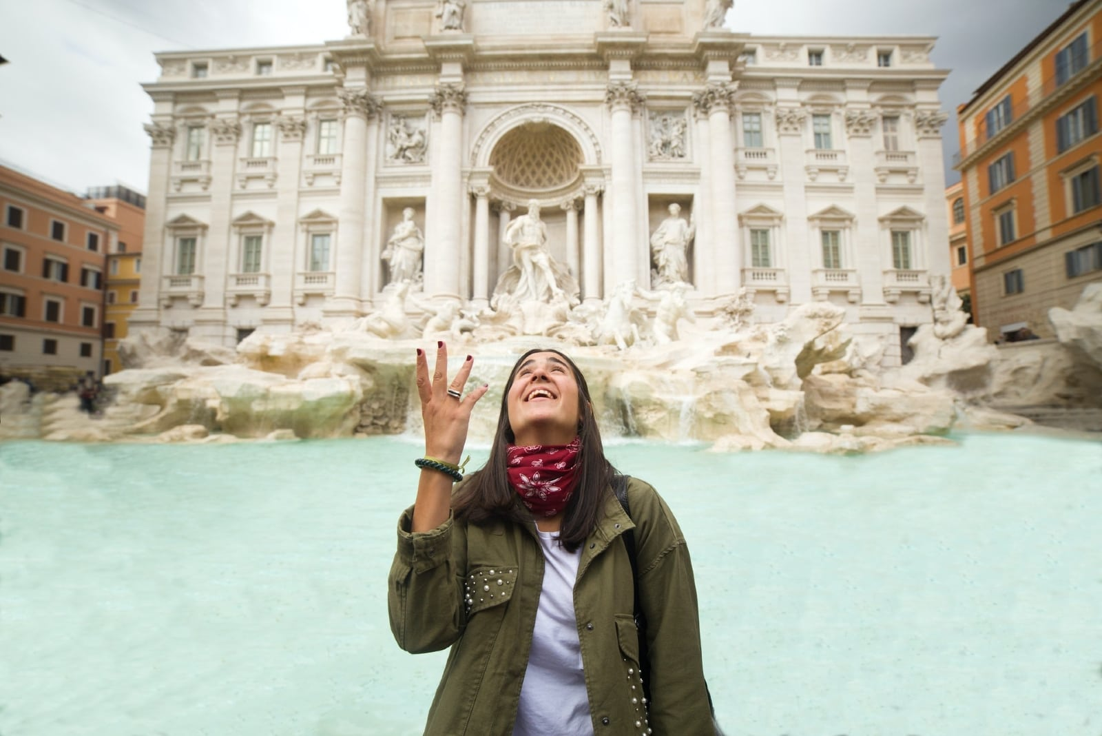 happy woman throwing coin in trevi fountain