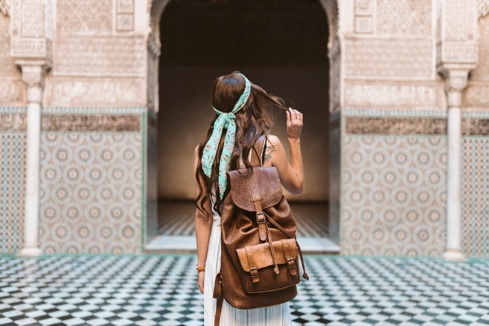 woman with brown backpack touching her hair