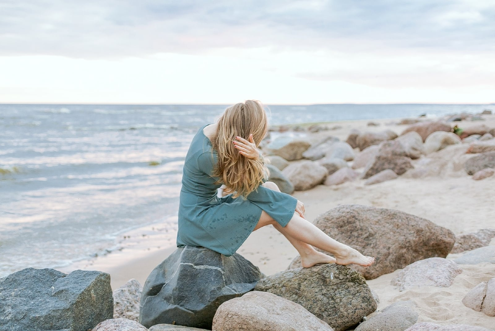 woman touching her hair while sitting on rock