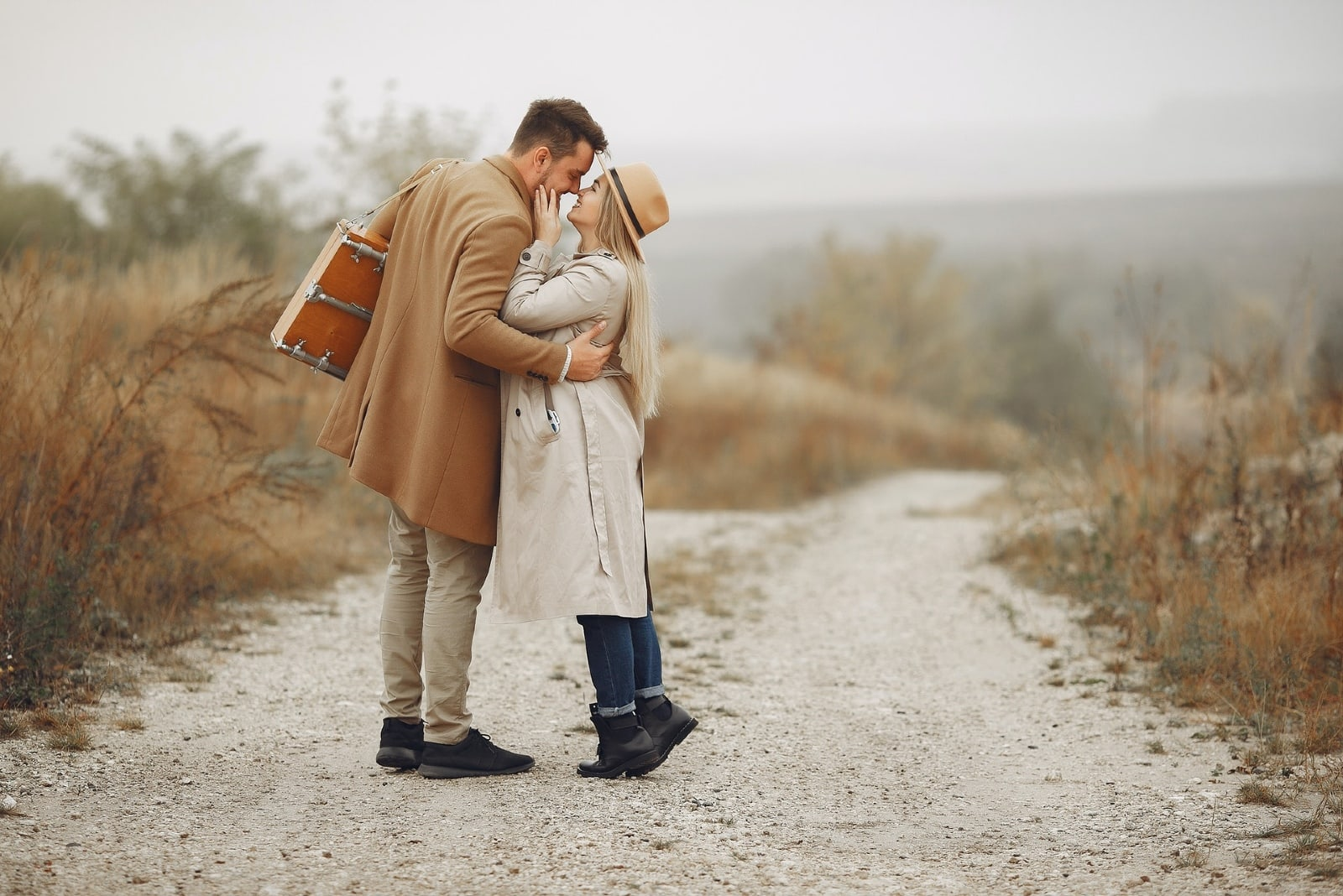 woman touching man's face while standing on rural path