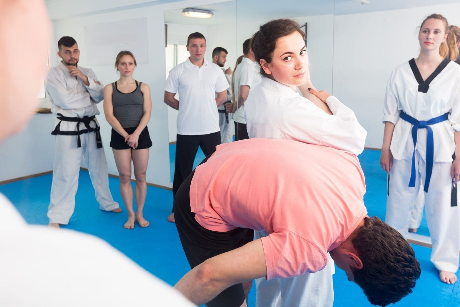 woman trainor showing defense method in training taekwondo in front of students