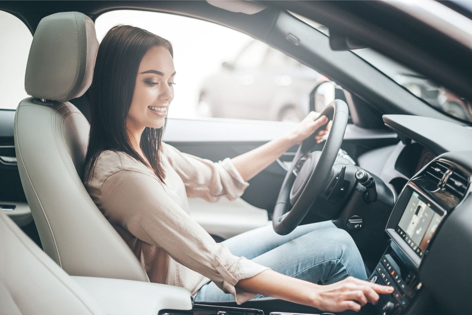woman turning the radio on of the car before driving