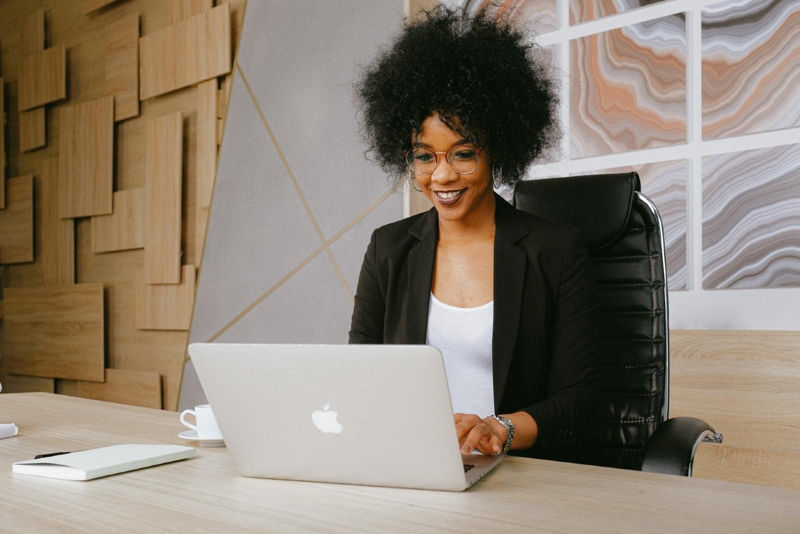 woman in black blazer using laptop in office
