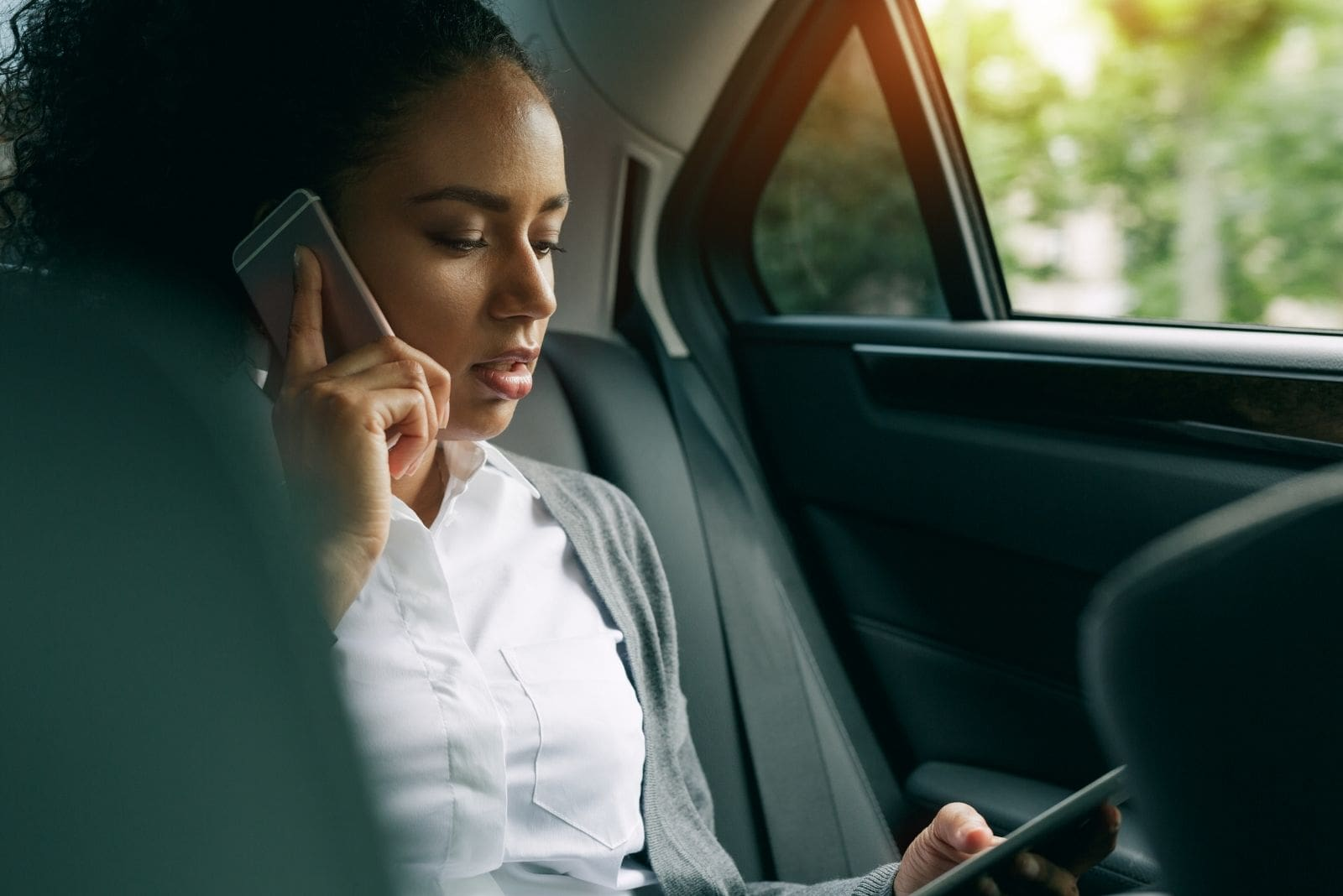 woman using phone in calling and browsing on the other inside the car sitting at the backseat