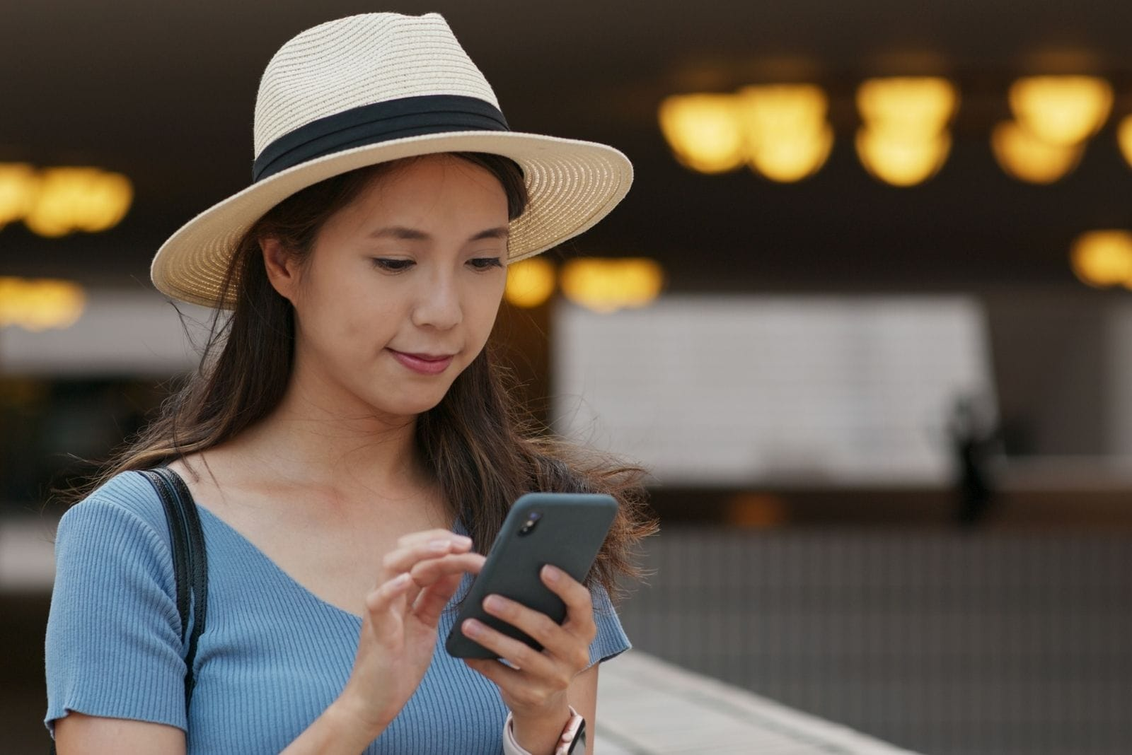 woman using smartphone with asian descent wearing hat