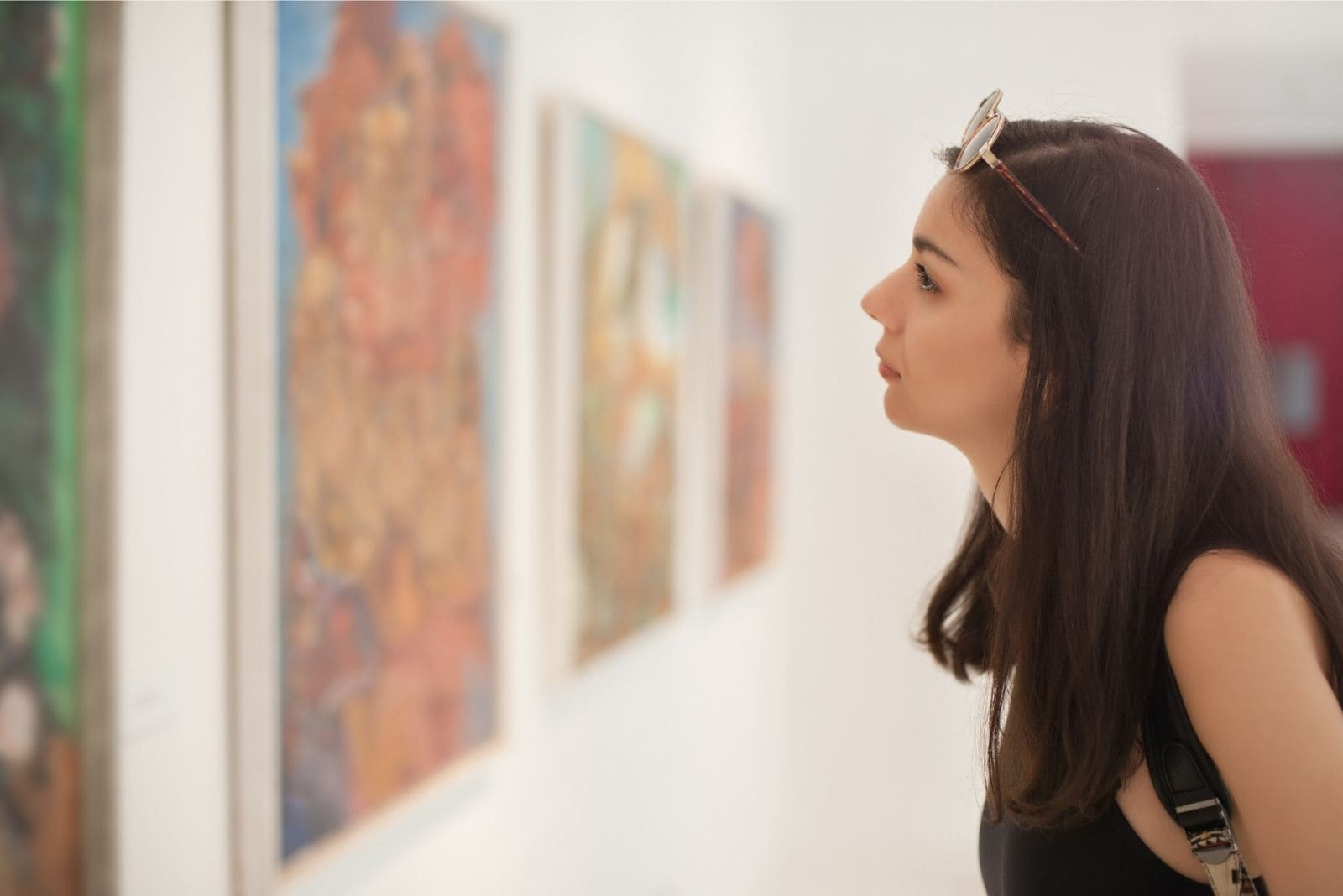 woman visiting an art gallery with arts on the wall
