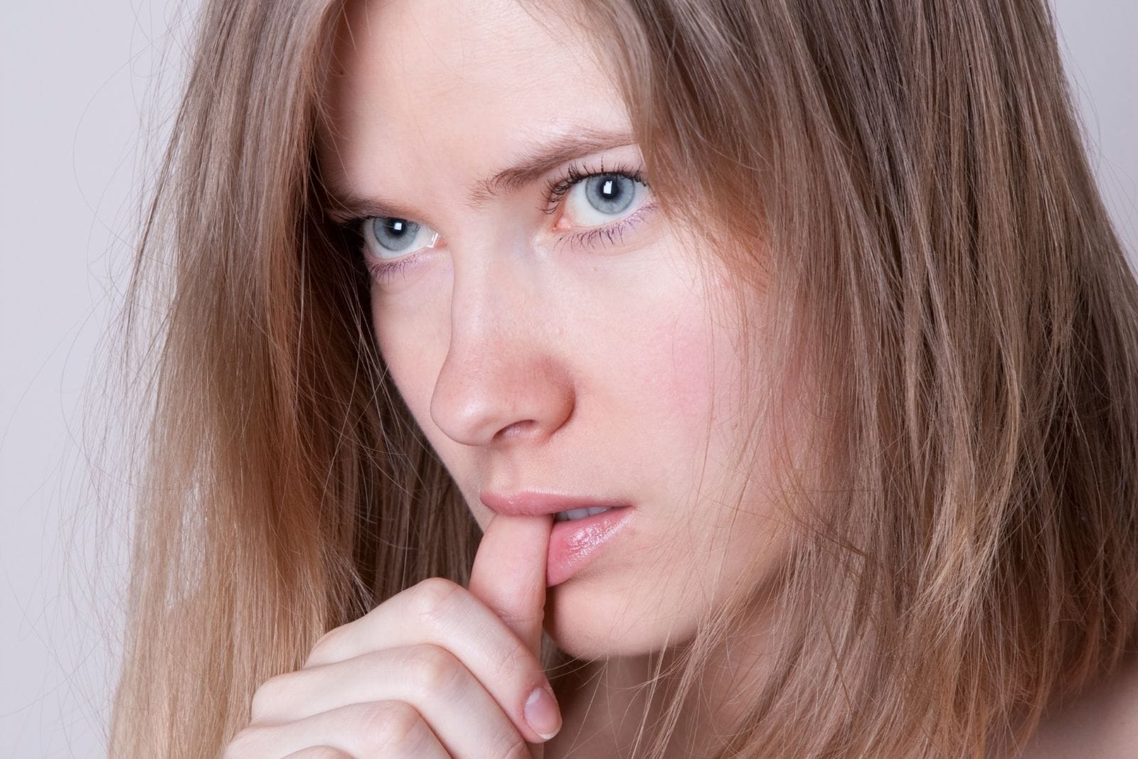 woman with a blue eye looking furiously biting her thumb