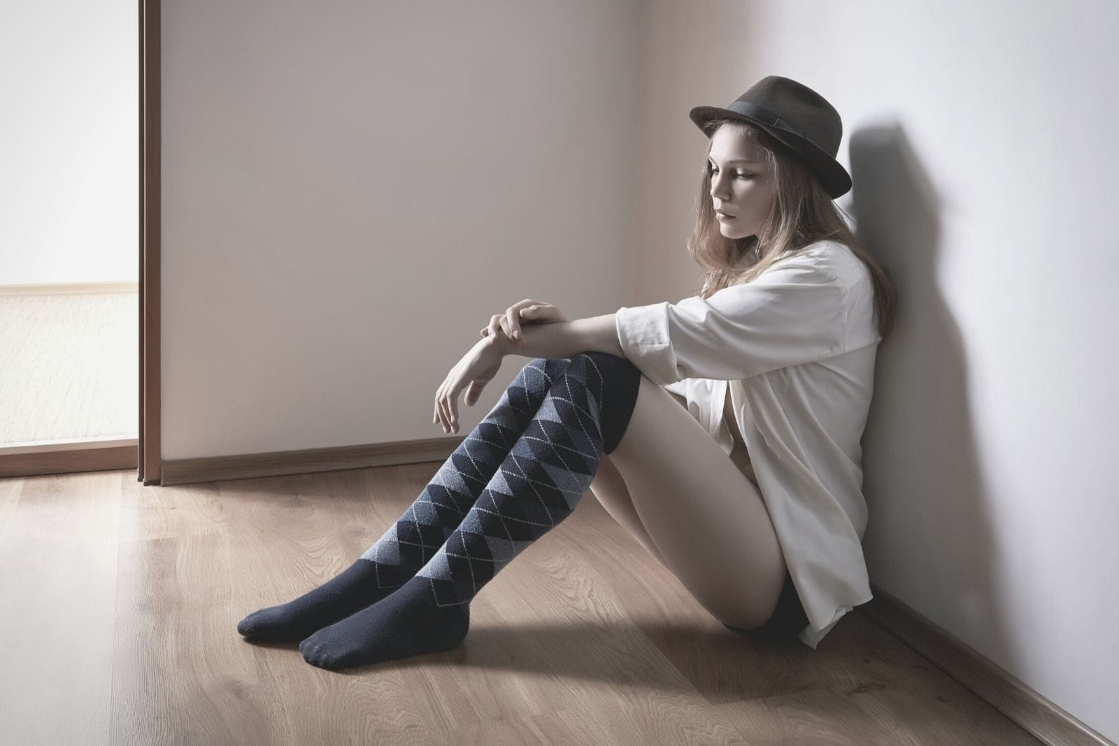woman with a hat sitting on the floor inside the room looking sad