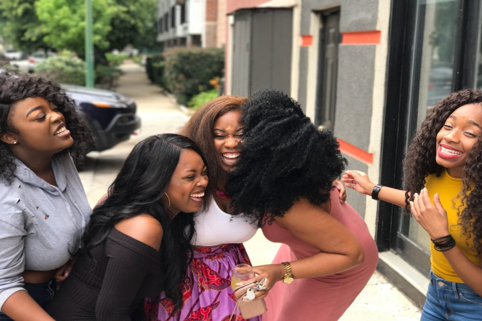 five women laughing while standing outdoor