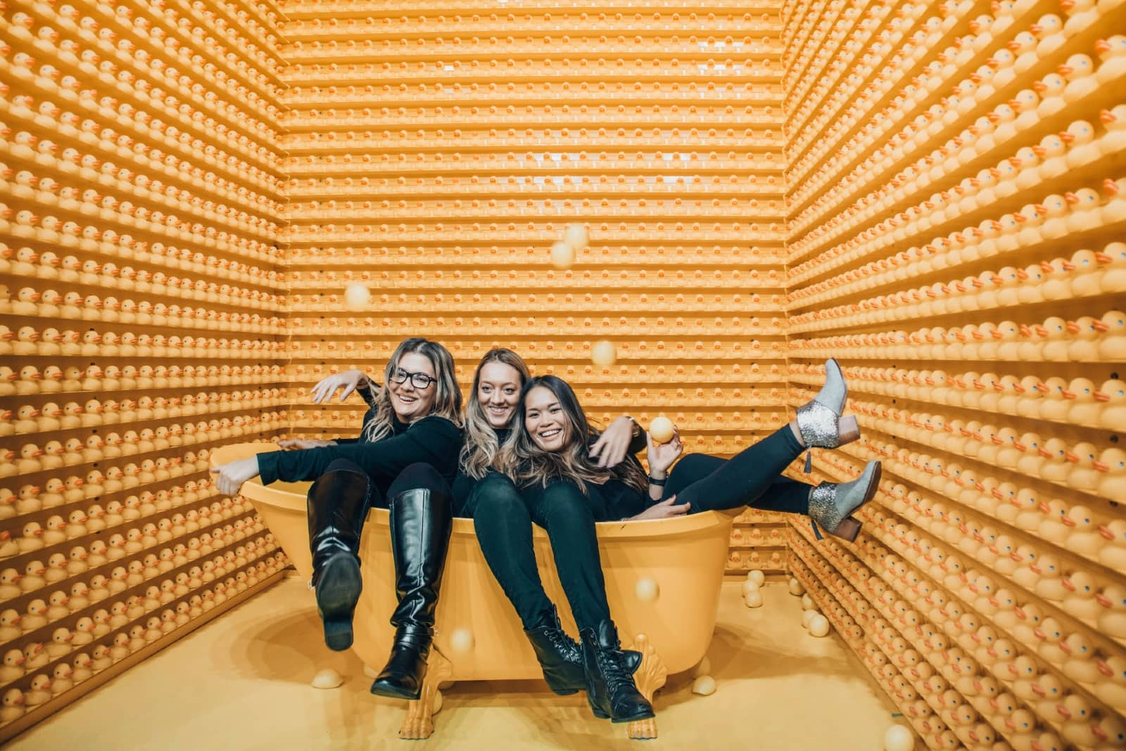 three women smiling while sitting in orange bathtub