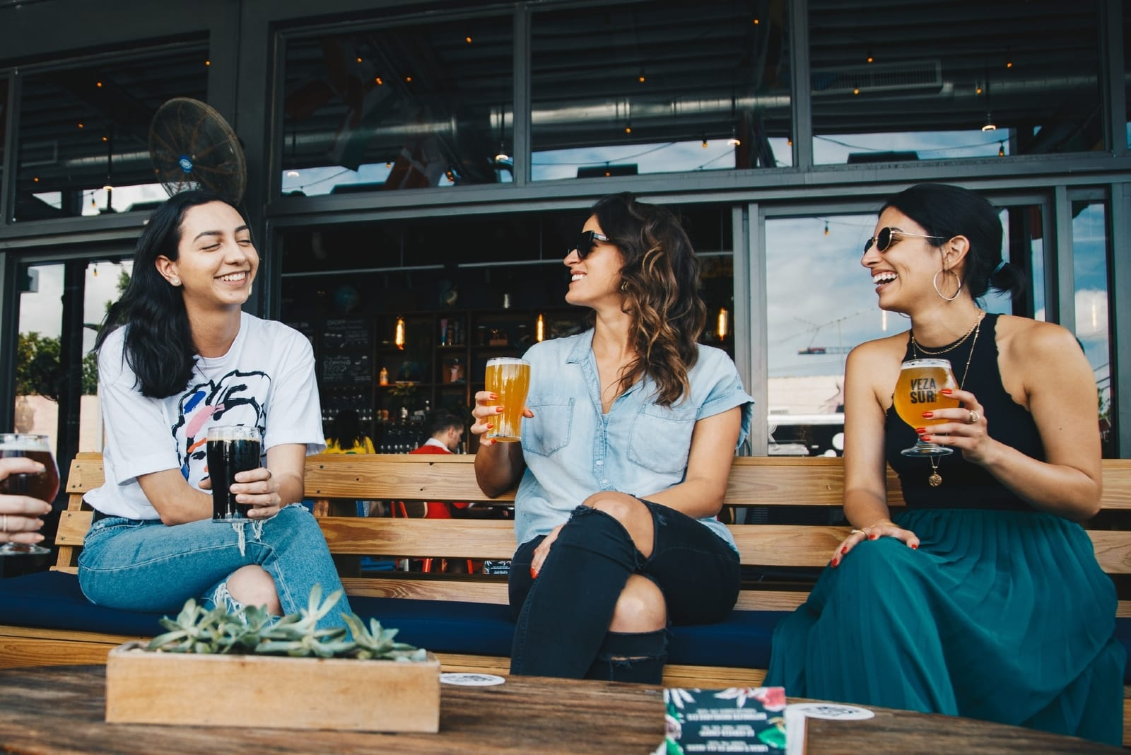 three women holding glasses of beer while sitting on bench