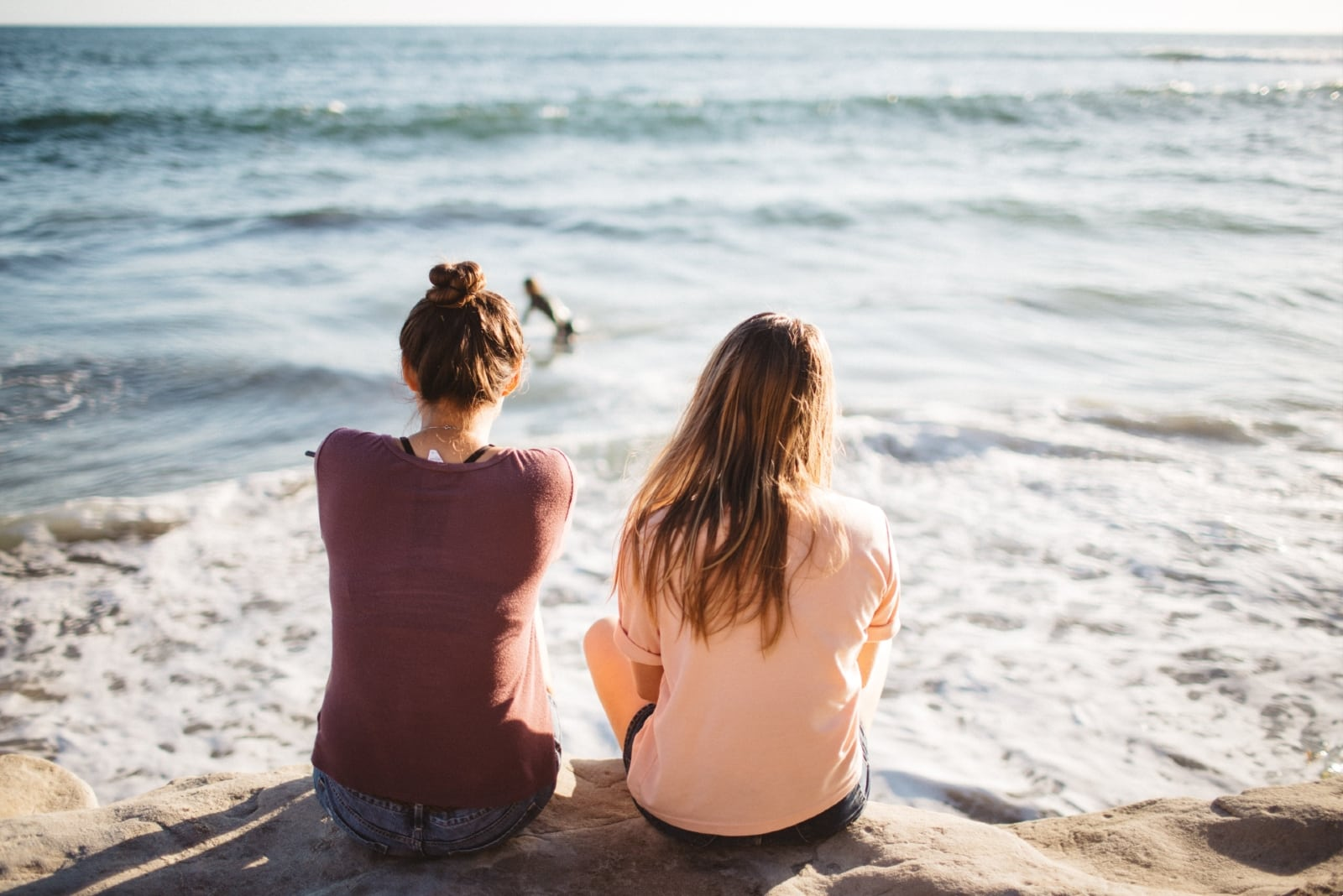 two women sitting on cliff looking at sea
