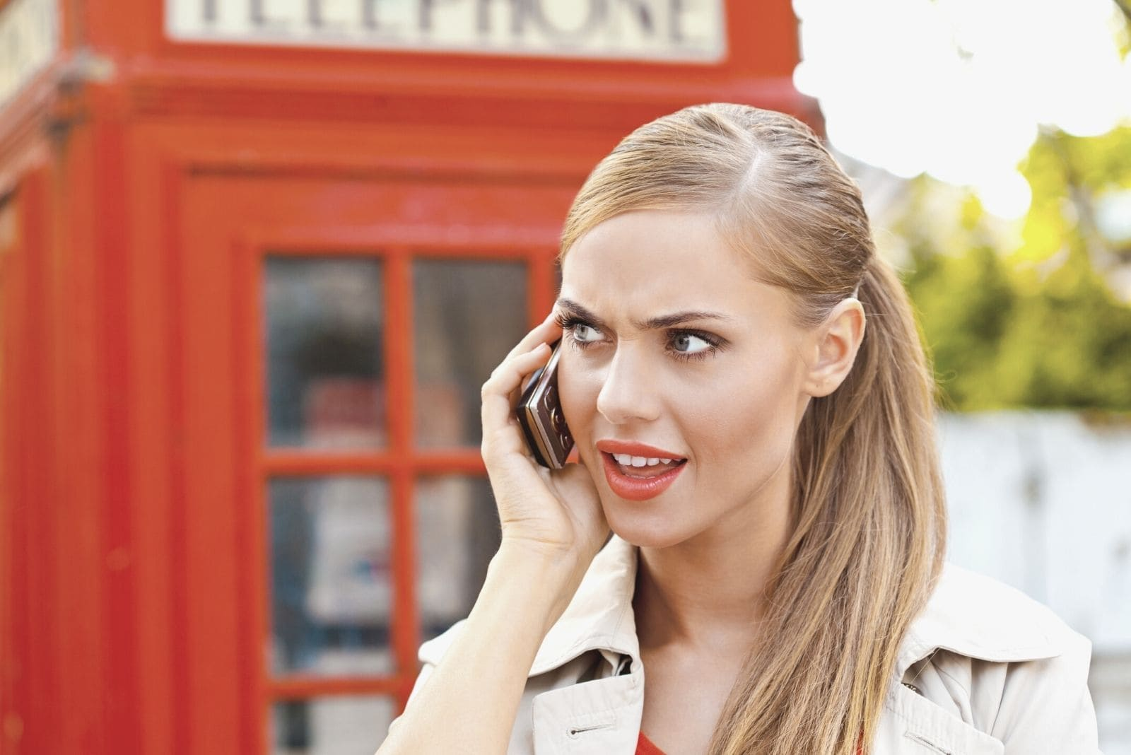 worried woman talking by the smartphone standing near a telephone booth in Europe