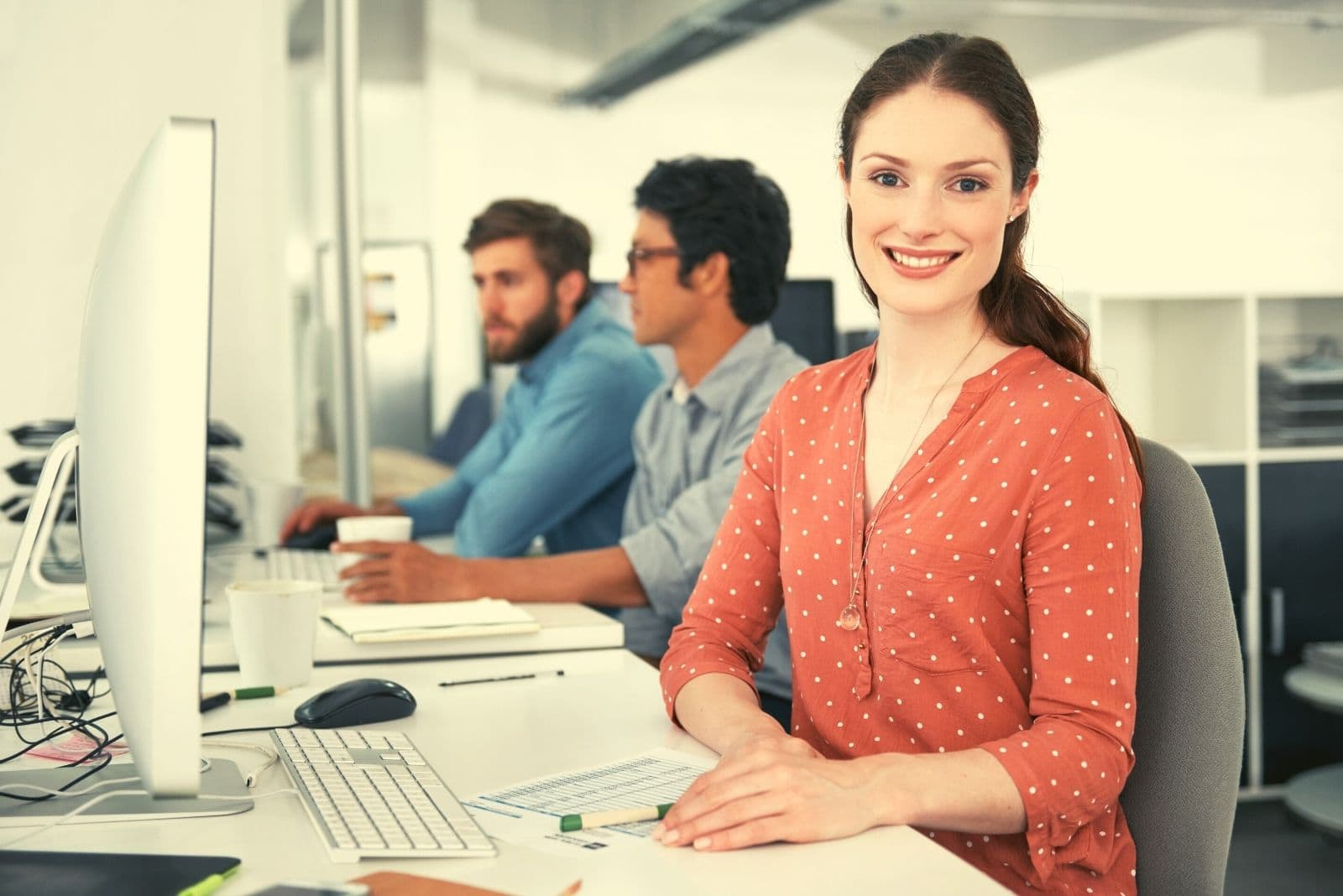 young businesswoman working in the desk with a positive mindset and other 2 two male colleague working beside her