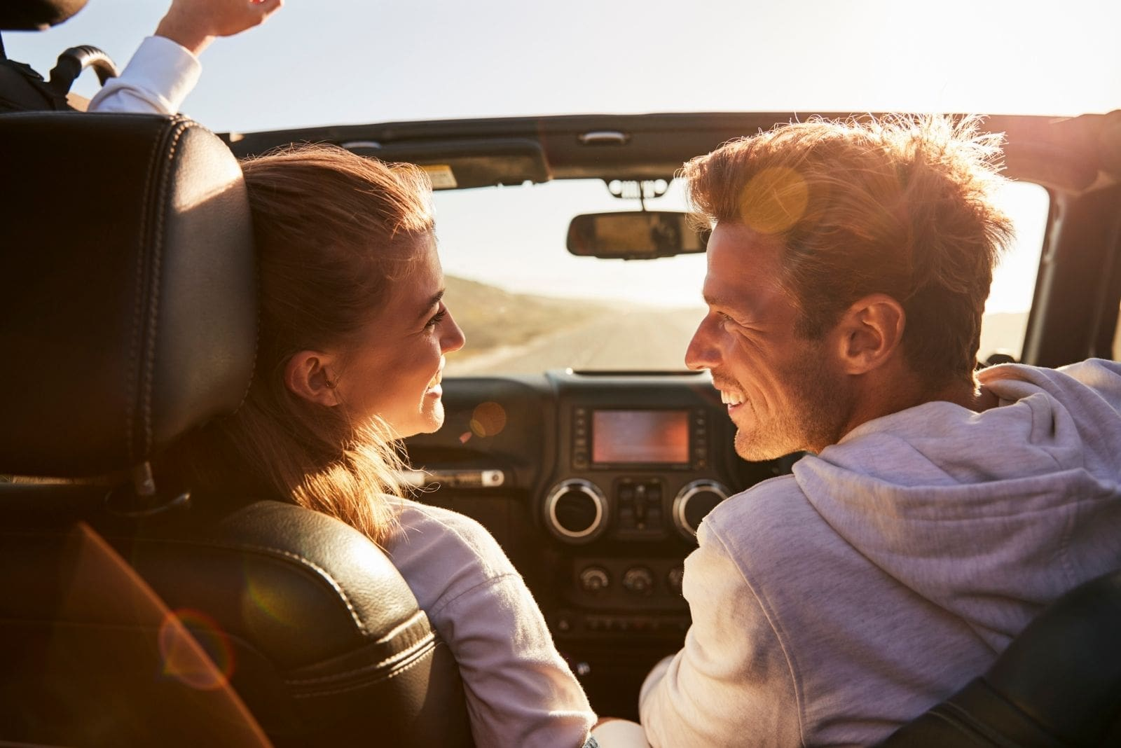 young couple glancing at each other while driving on open top car