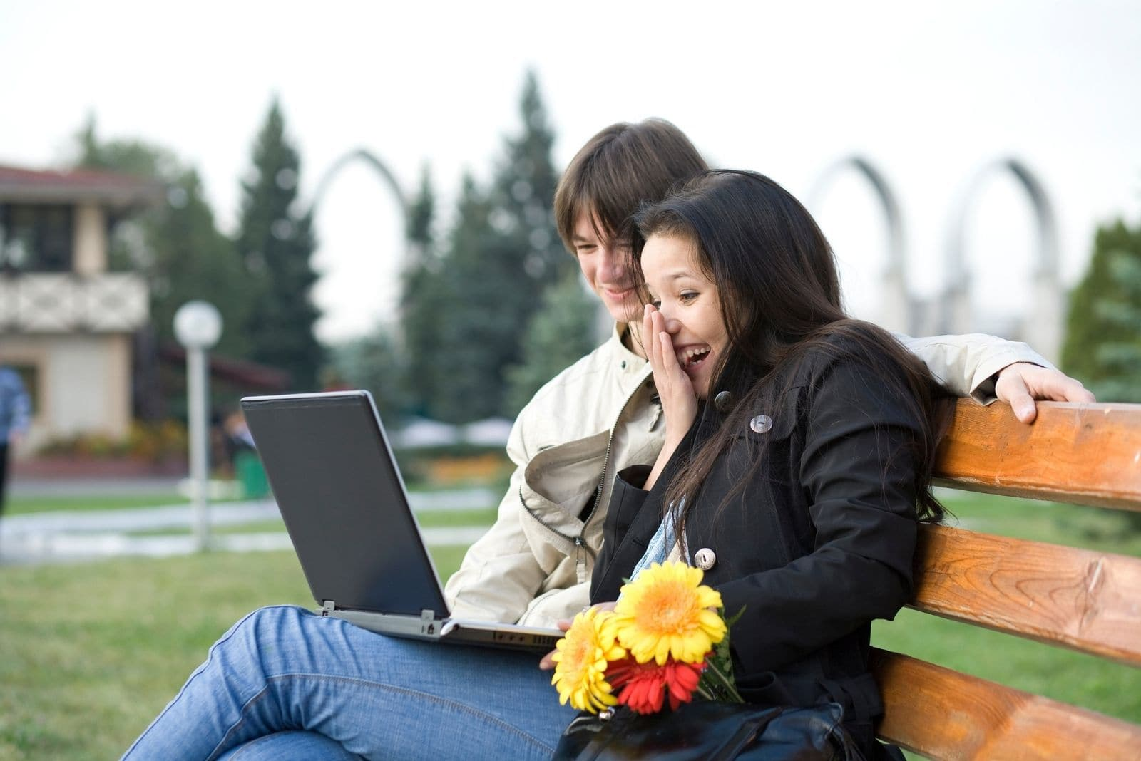 young couple watching movie on laptop while sitting on the bench outdoors