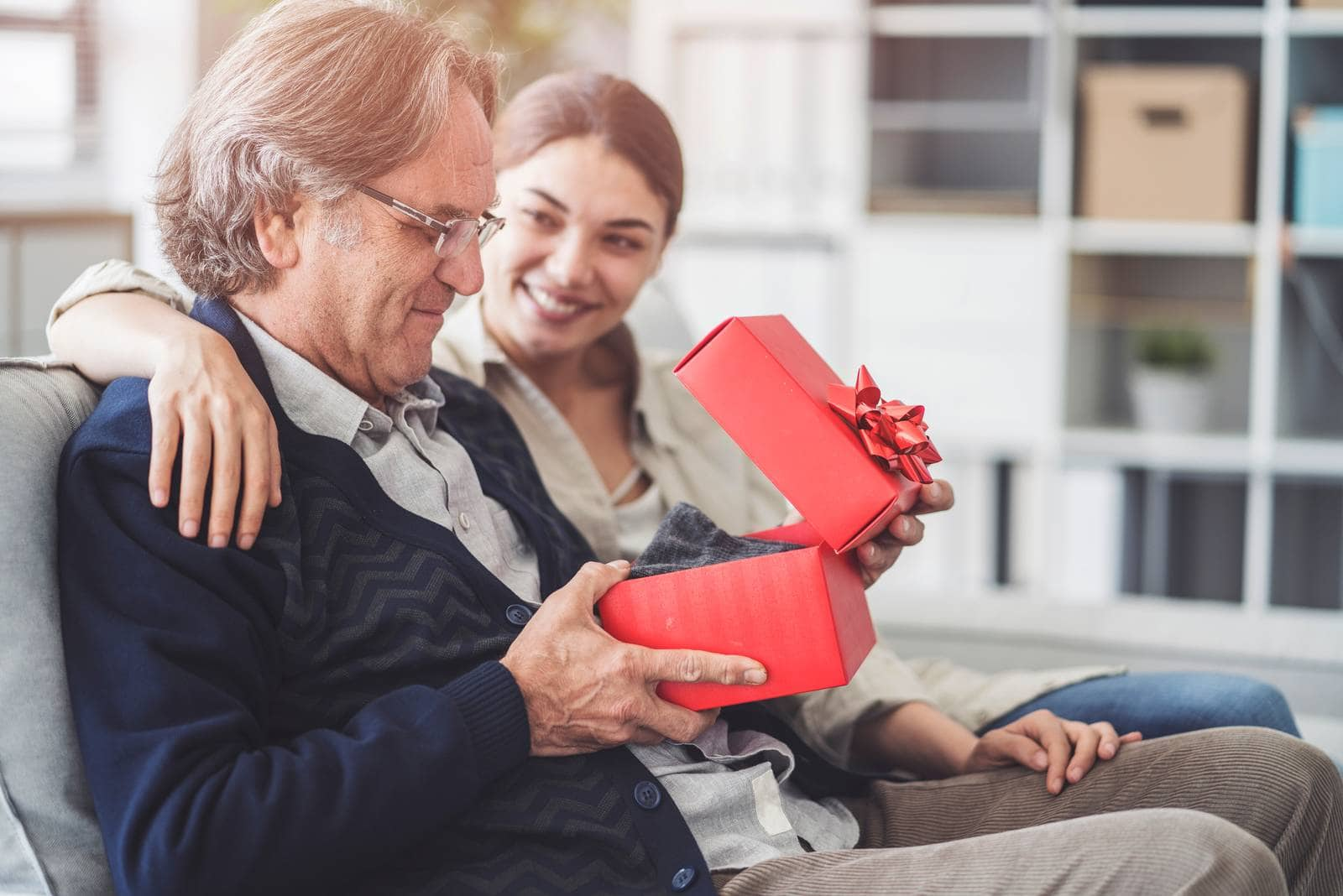 young loving daughter giving gift to her father sitting on the couch inside living room