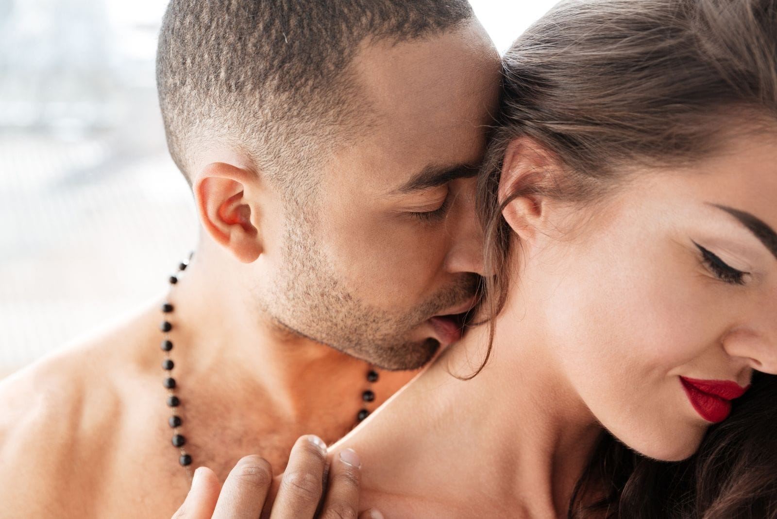 young man kissing passionately the woman's neck