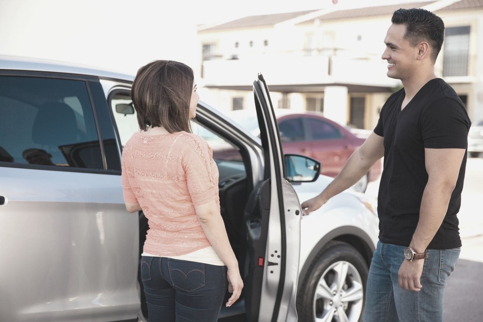 young man opening door of the car for a woman