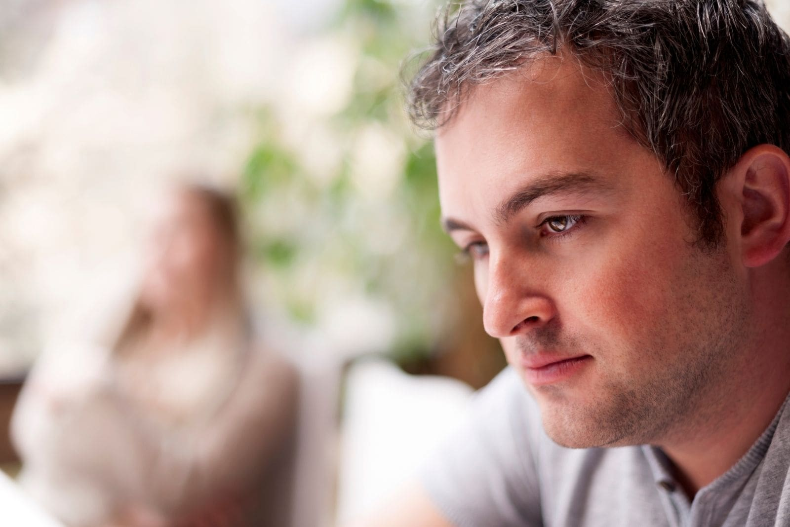 young pensive man focus on his face with blurry image of a woman apart from him