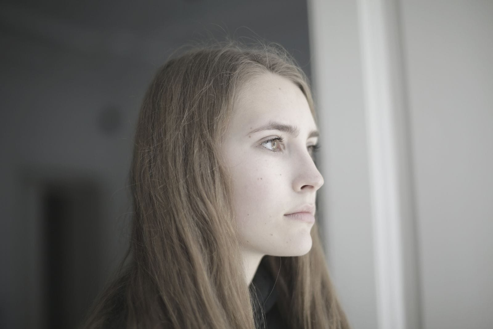 young pensive woman looking outside of the window