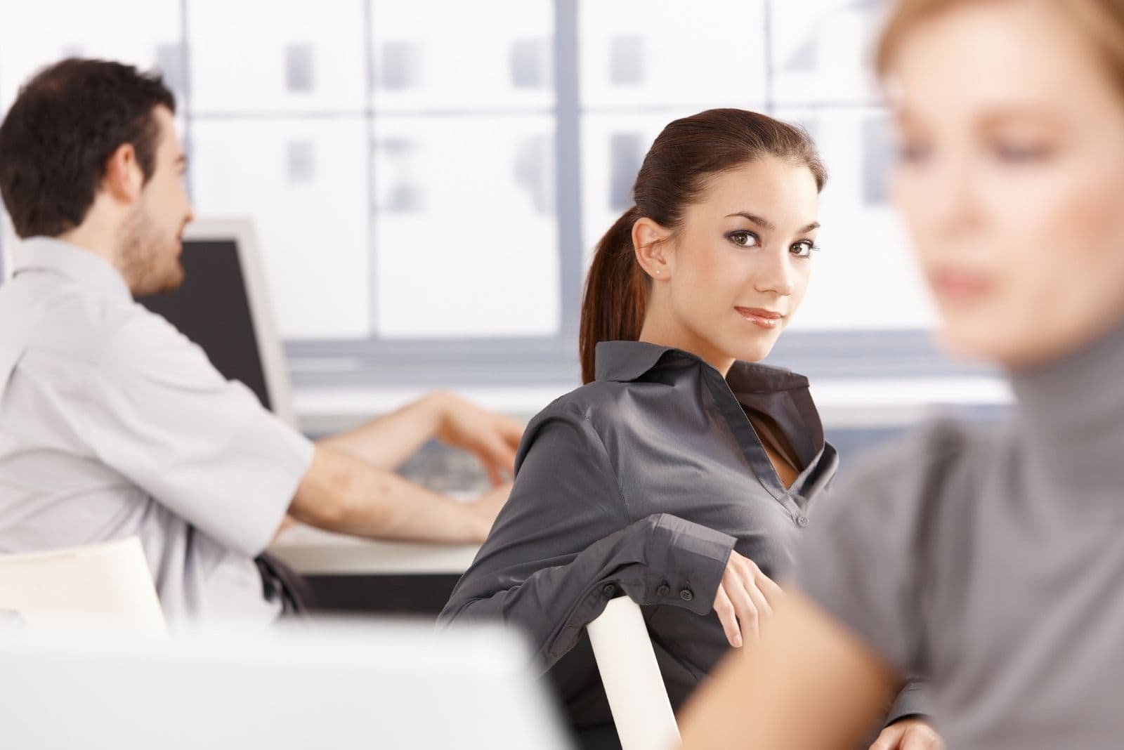 young people at office with focused on a woman smiling and looking at the camera