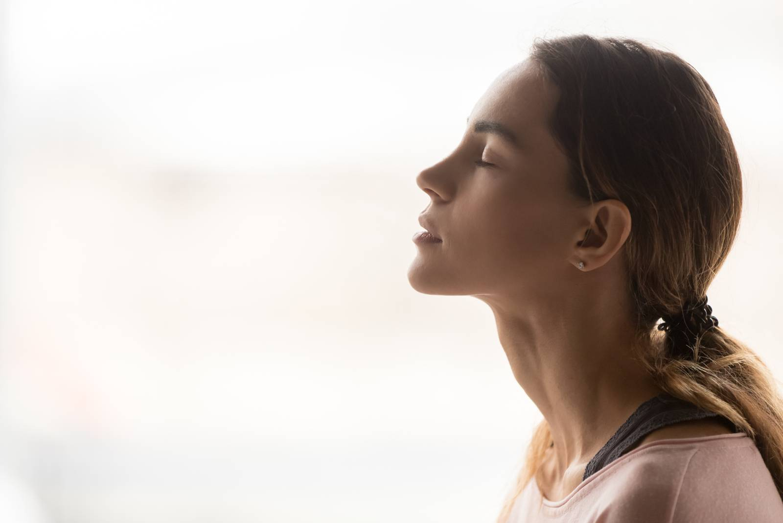 young serene woman closing her eyes with calmness