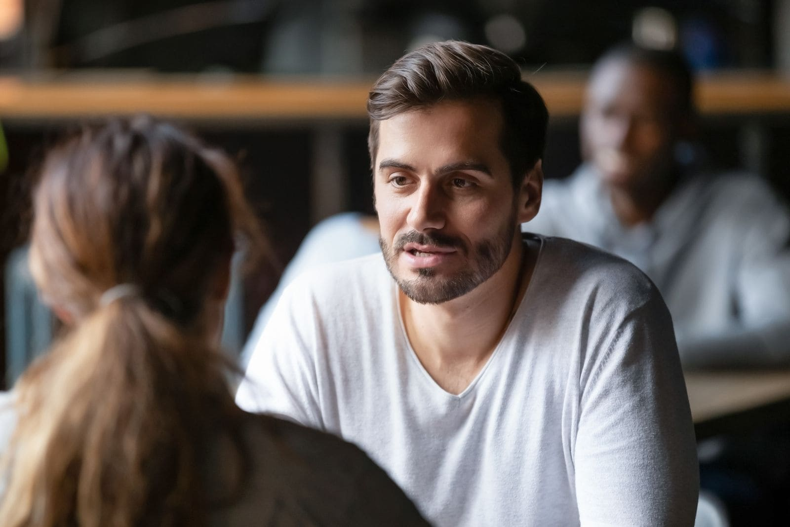 young serious man talking with a woman inside the cafe