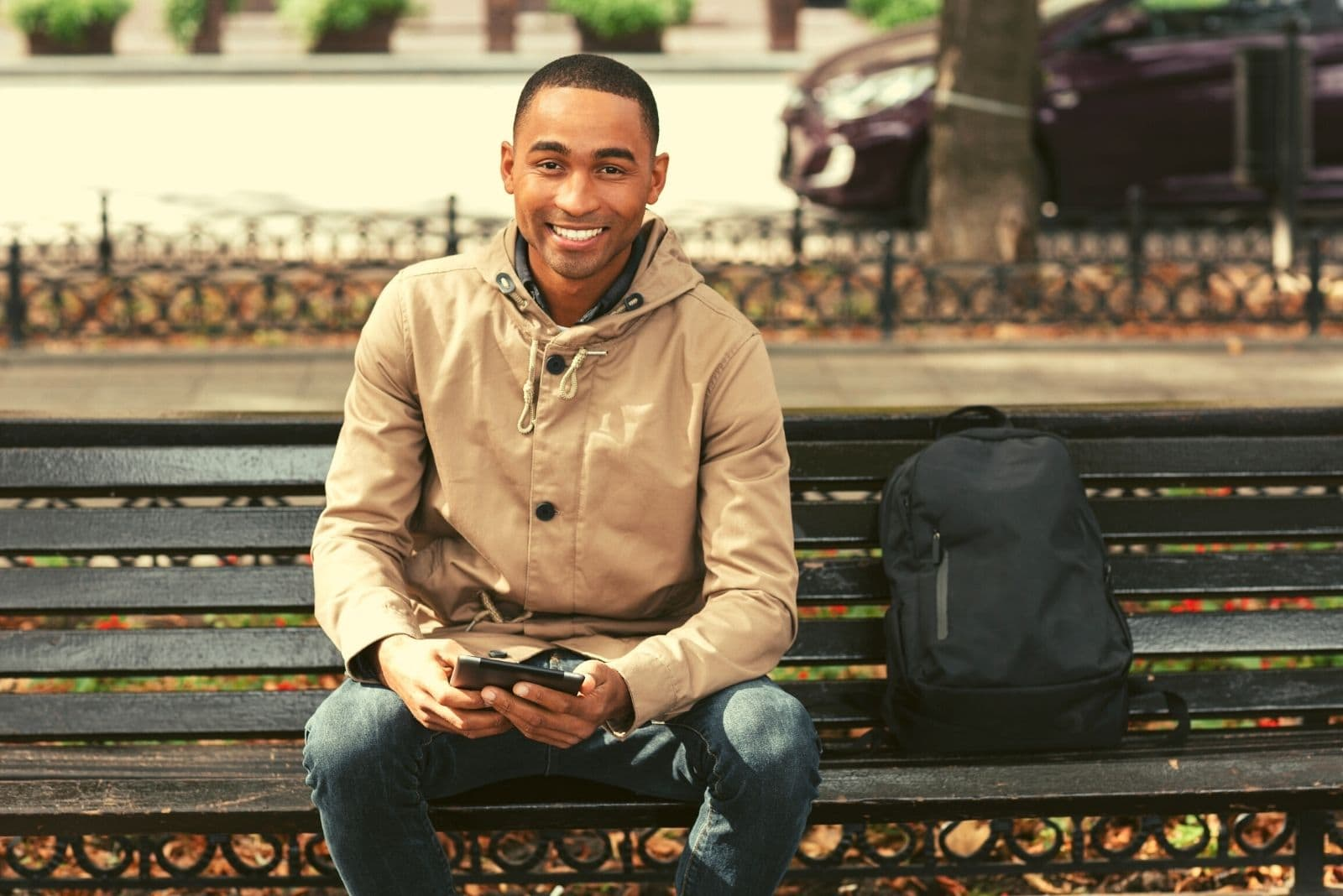 young smiling man using his tablet while sitting in the bench of the park and his bag beside him