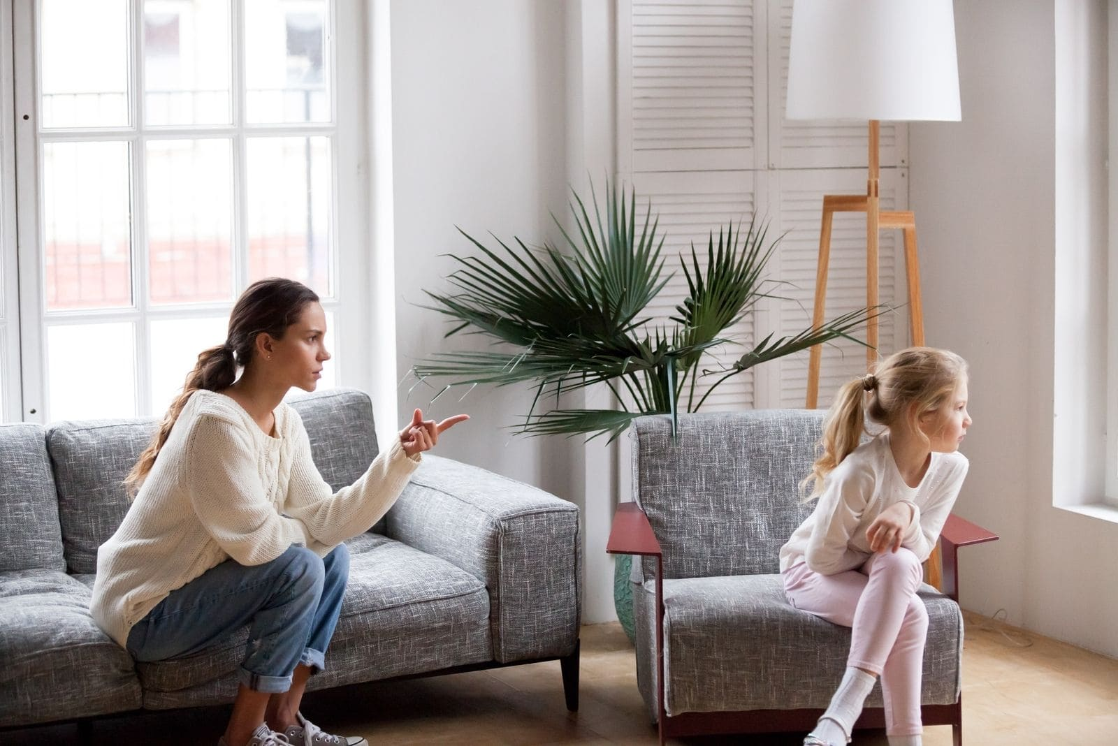 young strict mother scolding her stubborn child sitting inside living room