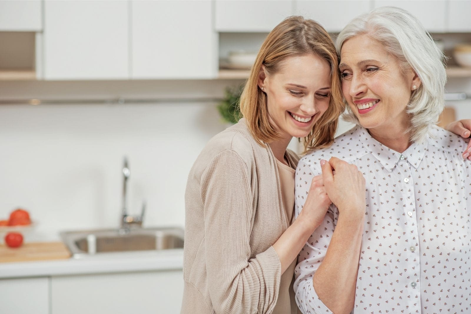 young woman cherished mature mother hugging her while both standing in the kitchen
