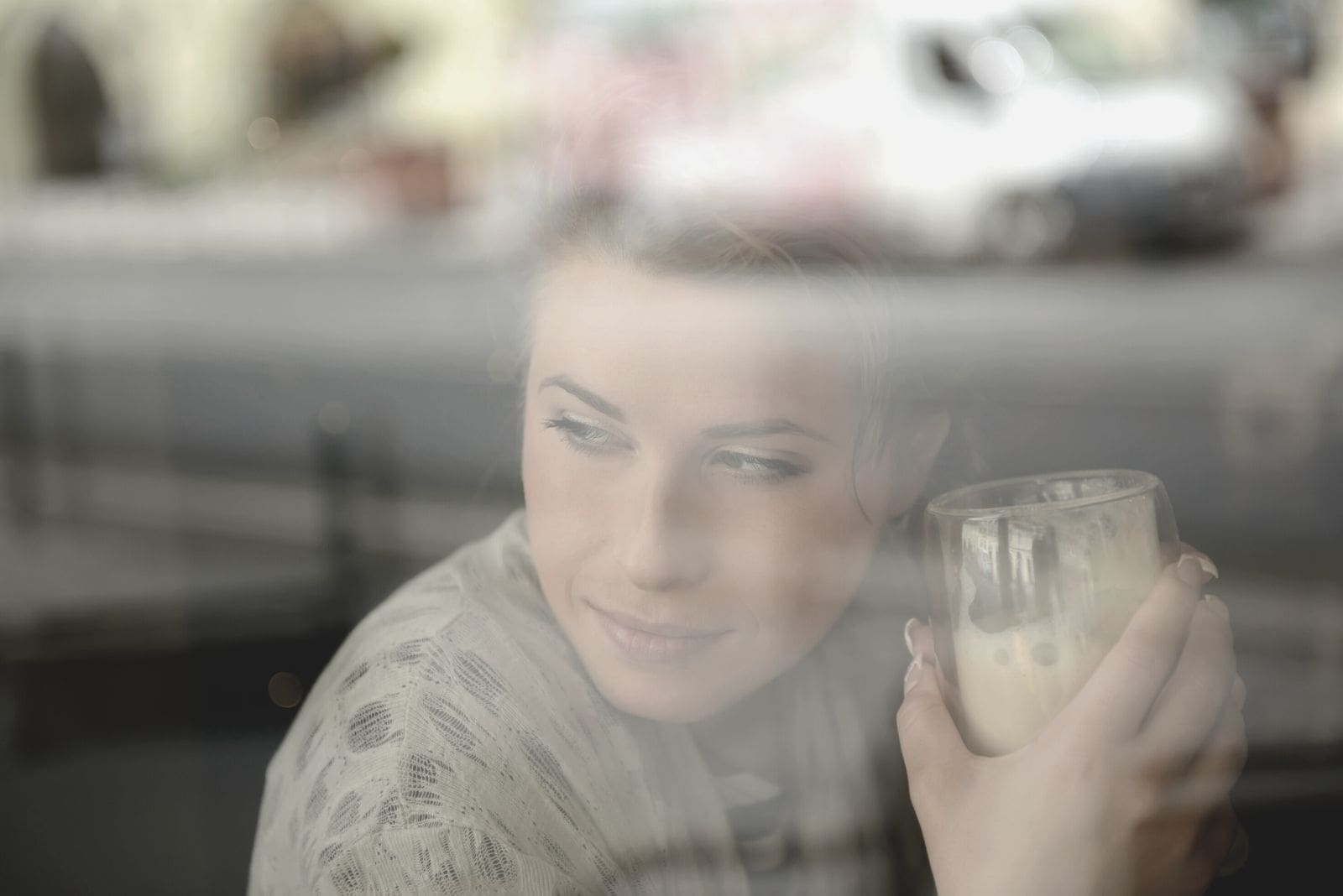 young woman holding a glass of frappe behind window thinking