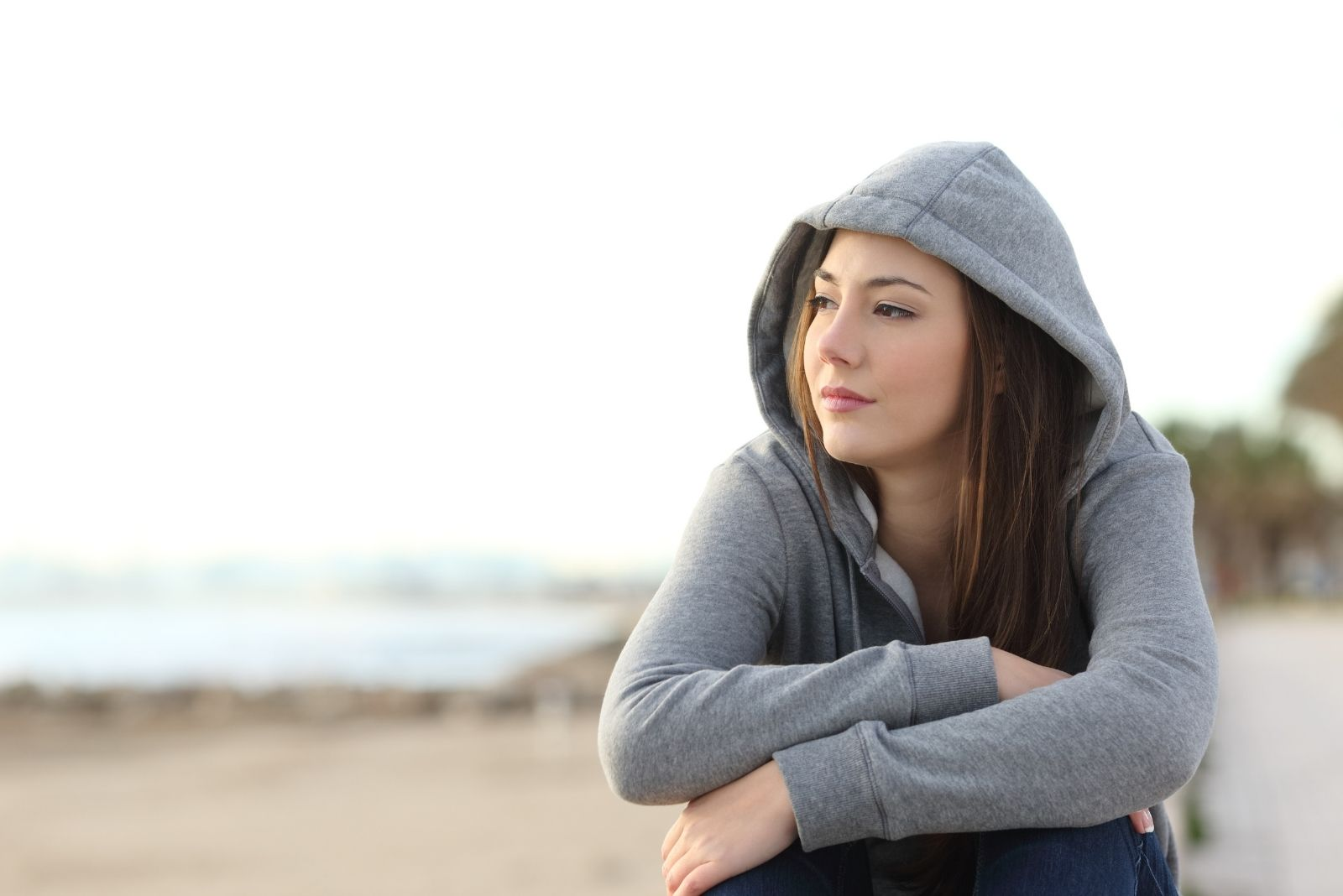 younng woman in a hoodie sitting on the beach thinking deeply