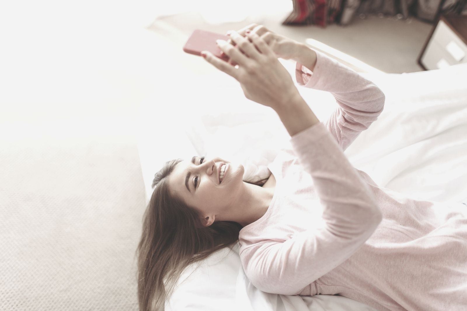 young woman lies in bed smiling and looking at her smartphone in the morning