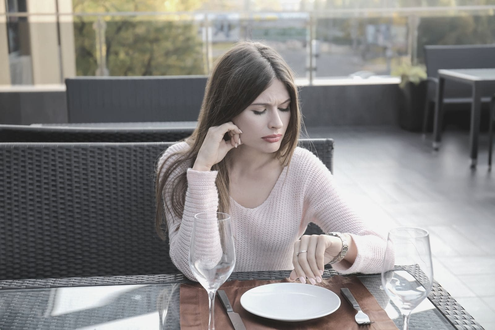 young woman looking at her watch while waiting for someone at the restaurant