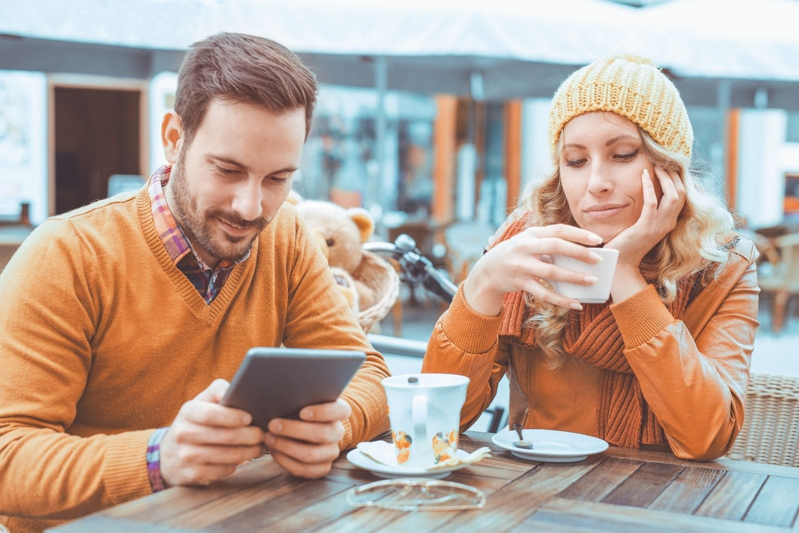young woman looks suspicious while boyfriend is texting on smartphone while having coffee in an outdoor cafe