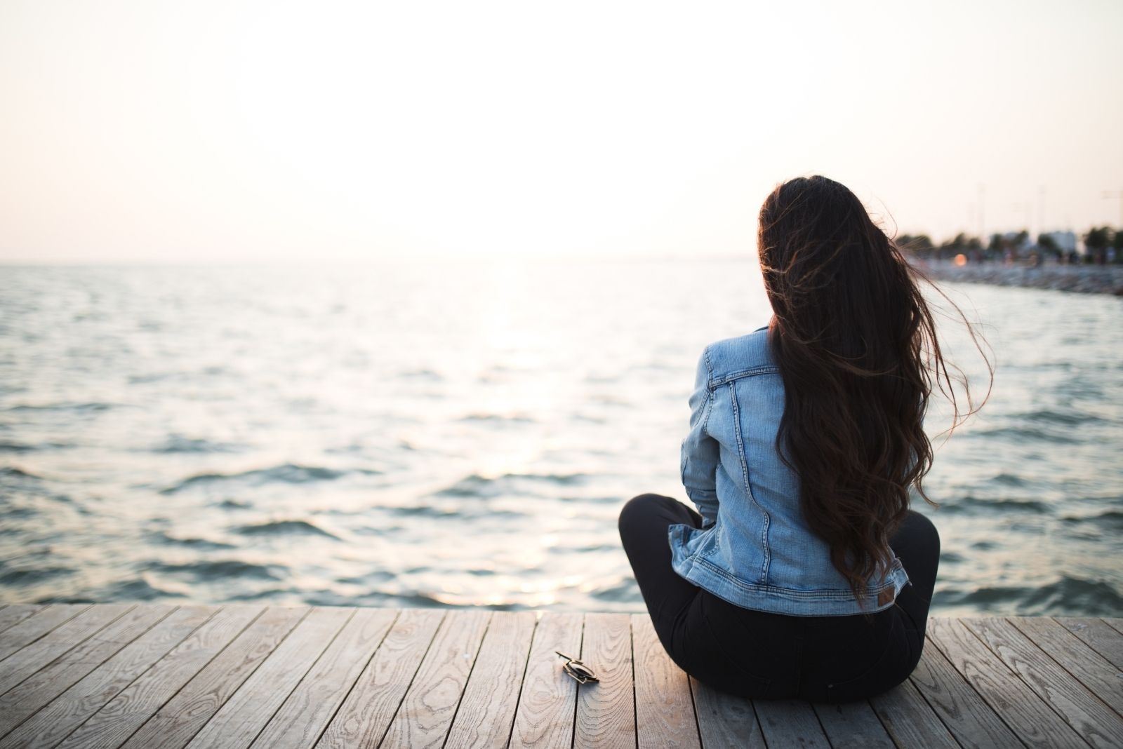 young woman sitting in wooden platform looking at the sunset