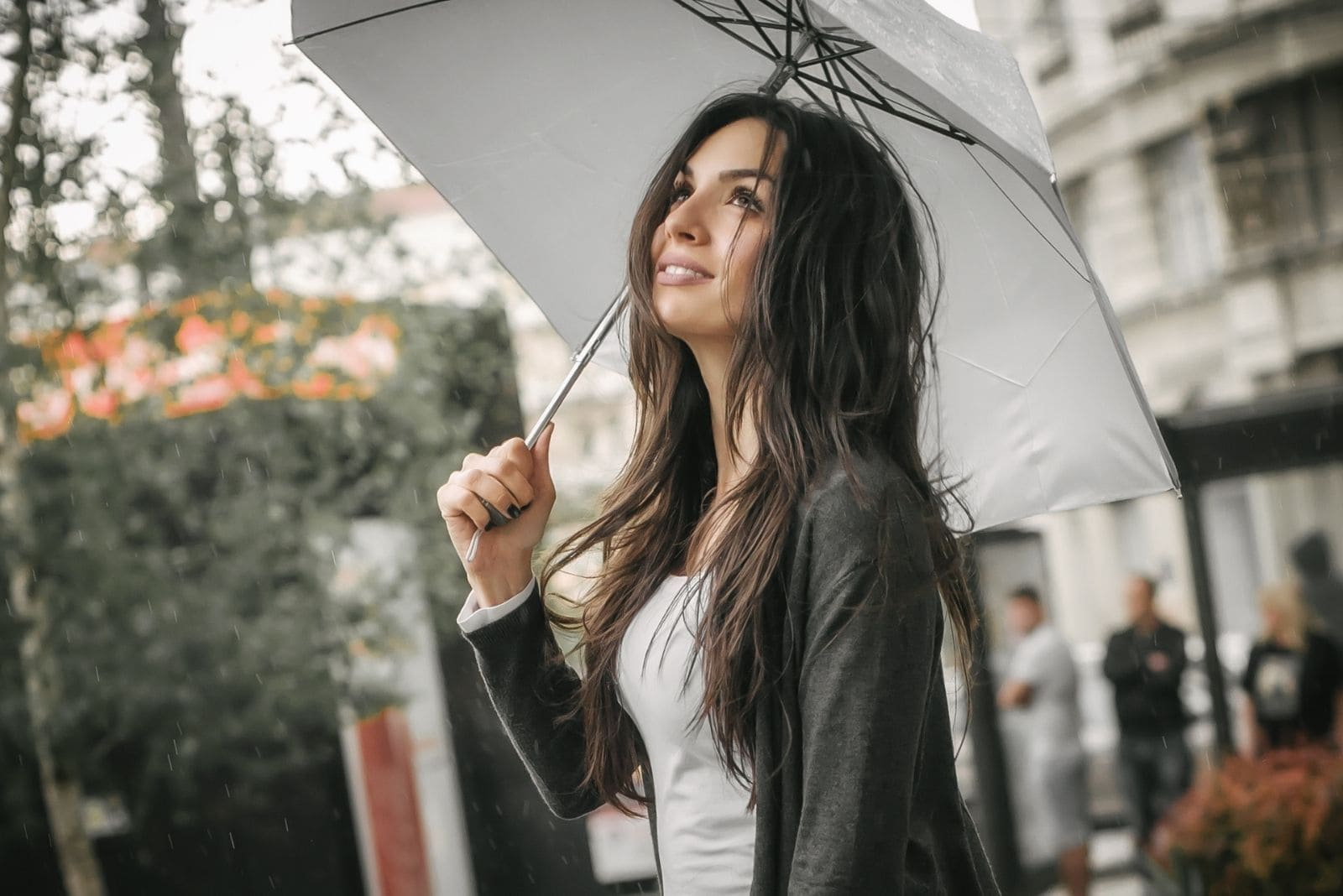 young woman smiling even its raining and bringing an umbrella outdoors
