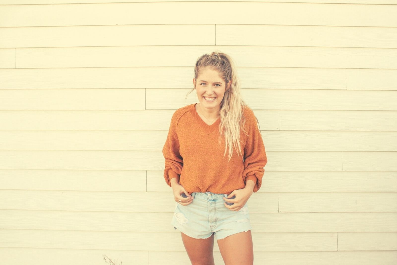 young woman standing against the white plank wall smiling and hands placed in the pocket of her short denim jeans