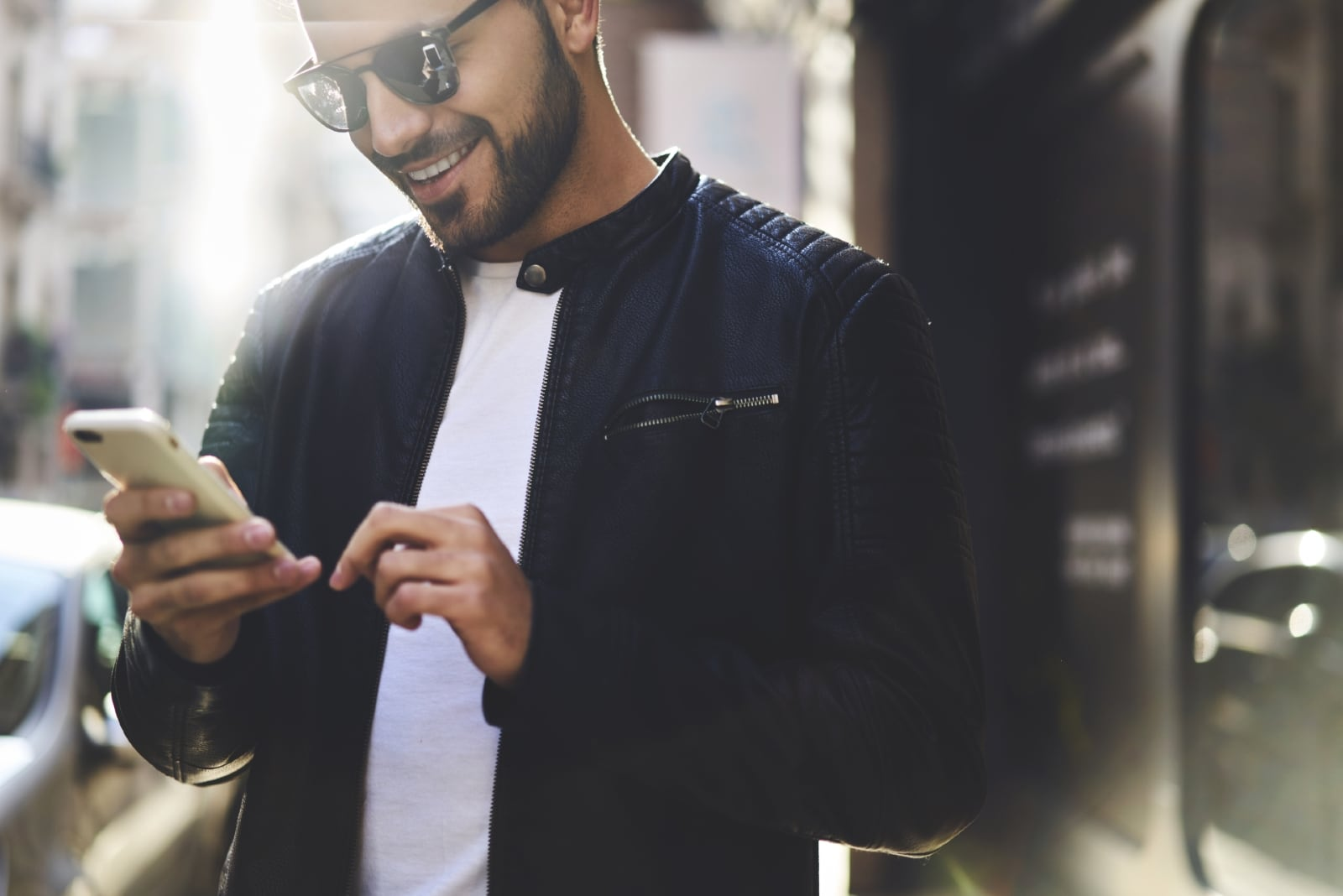 happy man in black jacket looking at phone
